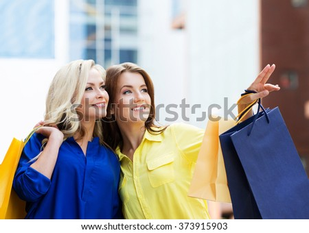 Gorgeous young brunette with beautiful young blond pointing at showcase of mall.