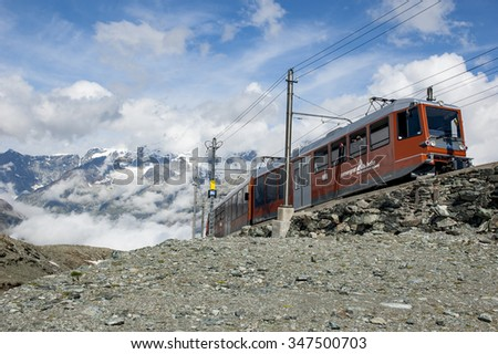GORNERGRAT, SWITZERLAND -  JULY 28, 2014 - Red train climbing up to Gornergrat station on the background of snow covered Alps and glacier