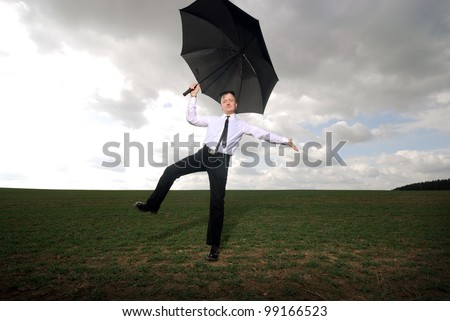 goth guy in business clothes dances with an umbrella on a meadow