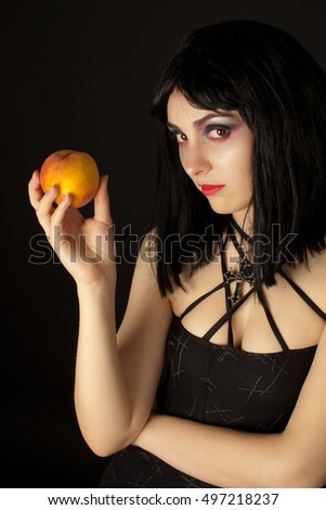 Gothic woman with halloweeen make up holding  peach