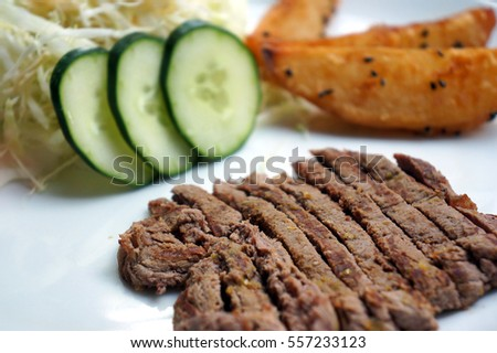 Gourmet grilled steak flavoured with potatoes and fresh cucumber