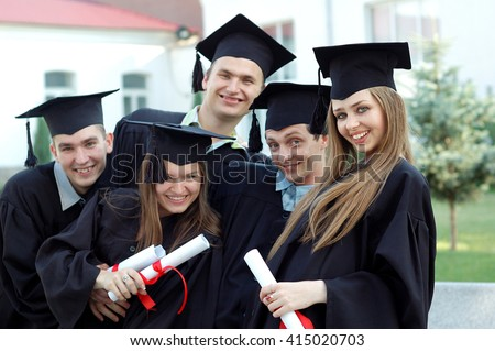 Graduates embrace, enjoy and look at the camera on the graduation ceremony. Happy graduation day. 5 graduates hold his graduate diplomas in their hands.
