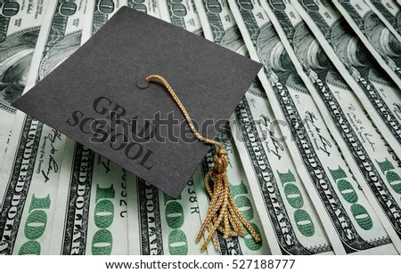 graduation cap with Grad School text on hundred dollar bills