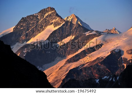 Grand Cornier south face (3962m) left, Weisshorn west  and south face  (4506m) centre and zinalrothorn west and south face (4221m) right in the swiss alps at sunset. seen from the Dents de Bertol.