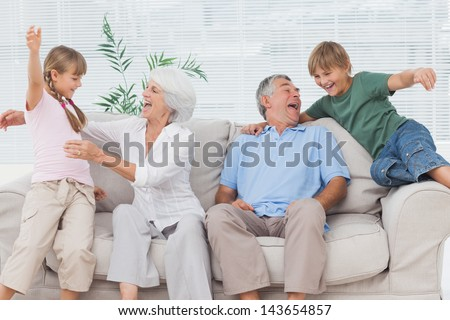 Grandchildren jumping on couch with their grandparents in the living room