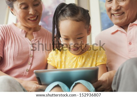 granddaughter playing on digital tablet with grandparents