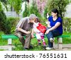 grandfather,little granddaughter and her mother in a park - stock photo