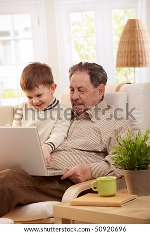 Grandfather together with grandson at home using laptop computer looking at screen.