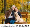Grandmother and child sitting on the bench in the autumn park  - stock photo