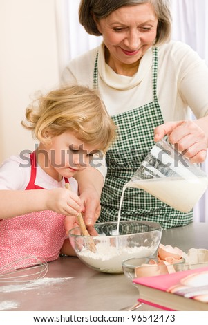 Grandmother and granddaughter baking cookies prepare dough