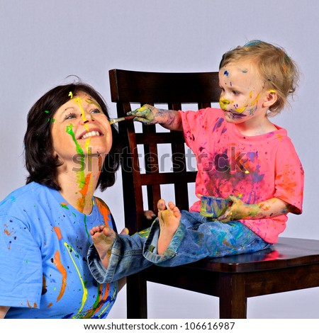 Grandmother is having fun letting her granddaughter paint her face. Both have paint all over their faces and clothes. Both seem to be enjoying themselves.