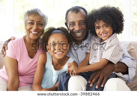 Grandparents With Grandchildren Relaxing On Sofa At Home Together