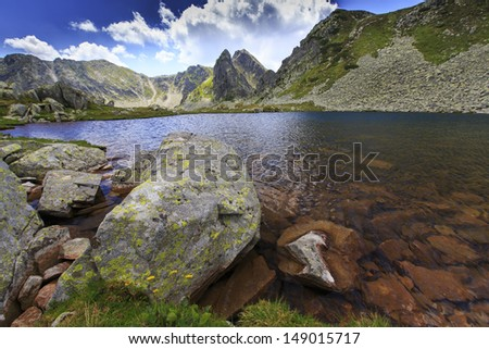 Granite rocks and mountain lake in the Alps, on a sunny day