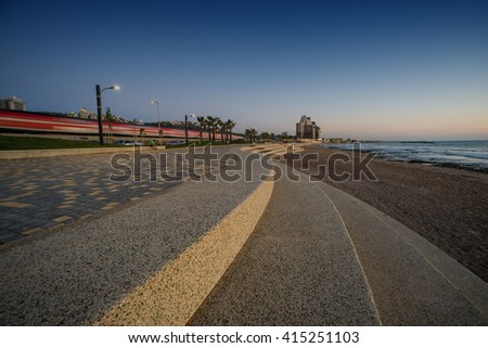 Granolite and paving stones covered front sea promenade with train passing behind