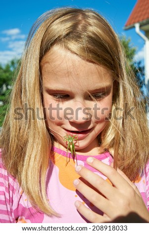 Grasshopper crawling across the face of a happy girl