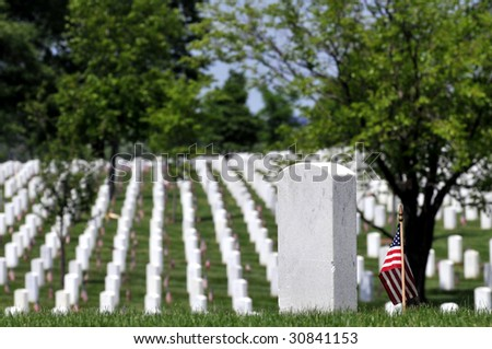 Gravestones decorated with U.S. flags to commemorate Memorial Day at the Arlington National Cemetery in Arlington, Virginia. One gravestone in the foreground with copyspace. Narrow DOF.