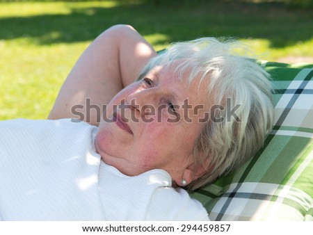 gray haired female senior is relaxing in the garden