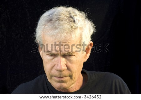 Gray haired man looking downward concentrating or glaring
