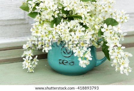 Great bouquet of fresh white cherry tree bird in a rustic blue cup on old wooden table . Green and white color. Floral decor elements