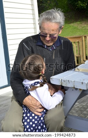 Great Granddad hug his great grandchild during home visit in his garden. Concept photo of senior citizen, retirement, pensioner, relationship,  health and aging.