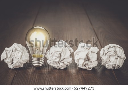 great idea concept with crumpled office paper and light bulb standing on table