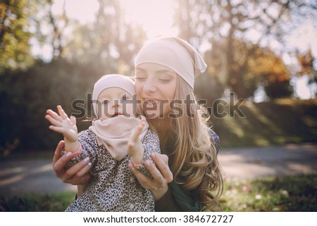great trendy young mothers walking in the park with his daughters in beautiful clothing