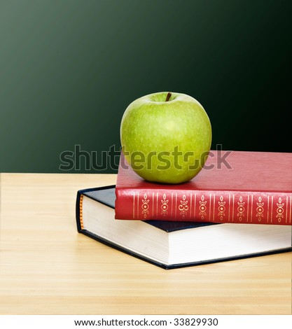 Green apple on top of books