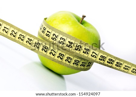 green apple with a measure tape diagonal