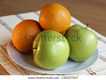 Green apples and oranges on a plate.