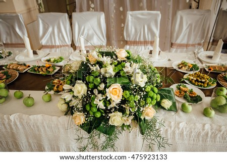 Green apples and white roses beautify wedding dinner table