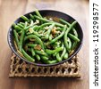 Green beans with almonds in wooden bowl - stock photo