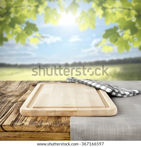 green blurred background of landscape at spring time and yellow top and napkin on top