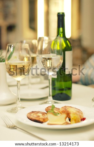 Green bottle of wine and two glasses with champagne and water also with dish anf fork on table in restaurant