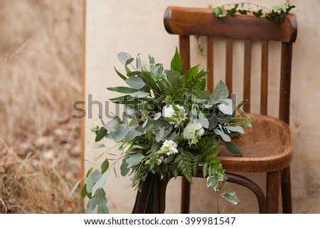 Green bouquet of eucalyptus, ivy, fern, aspidistra, ruskus, date fruit, pink, ranunkulyus with flax box, green and brown velvet ribbons on white stand and brown on wooden chair and beige background