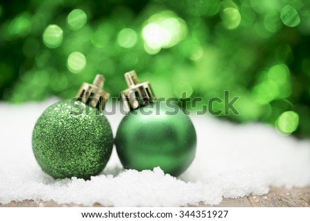 Green Christmas balls on snow against green bokeh background.