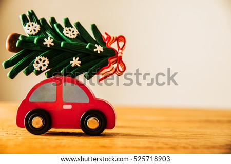 green Christmas tree on red toy car. Christmas holiday celebration concept. empty copy space for inscription. Holiday background.