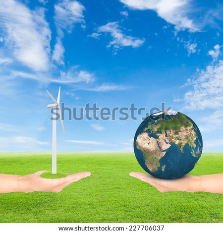 Green Earth concept,hand holding wind turbine and earth against green field and blue sky background.Elements of this image furnished by NASA