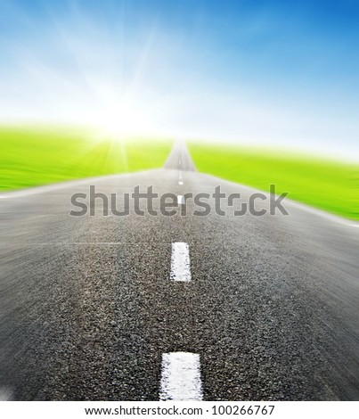 green field and road over blue sky in motion- travel and tranportation concept