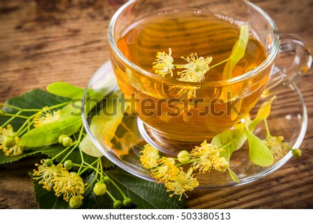 Green herbal tea with linden flowers on old wooden table, closeup