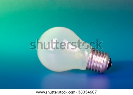 Green idea concept - light bulb on color background
