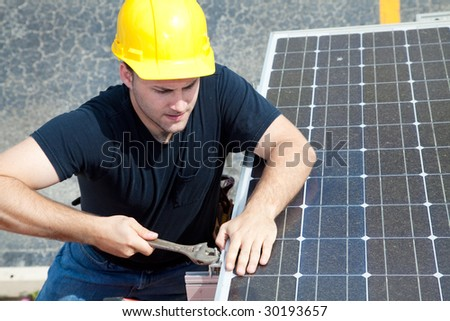 Green job series - young electrician repairs solar panel.