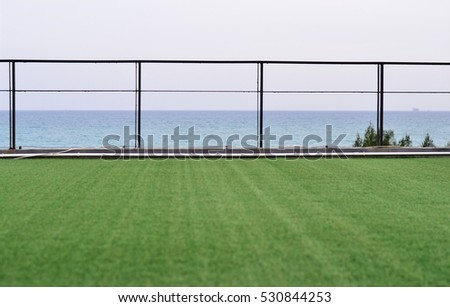 Green lawn with a view of the sea background.