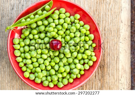 Green peas on the red plate
