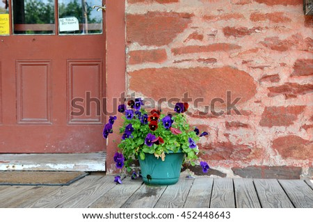 Green pot of pansies outside an old brick mill building