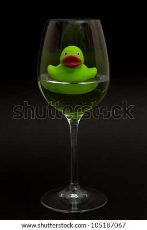 Green rubber duck in a wineglass with water (black background)