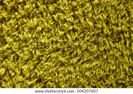 green shag carpet background detail with long yarn