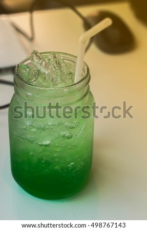 Green soda in a glass of water