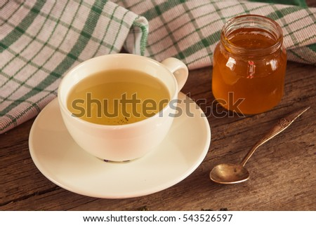 Green tea in a white cup and jar of honey with spoon and green kitchen napkin on wooden background