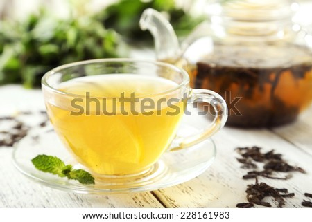 Green tea in cup and teapot on white wooden background