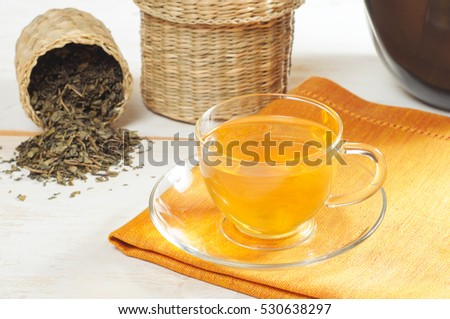 Green tea in the glass cup on the wooden background